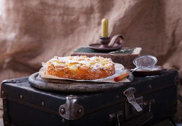 Apfelkuchen auf einem weinlesekoffer in puderzucker Premium Fotos