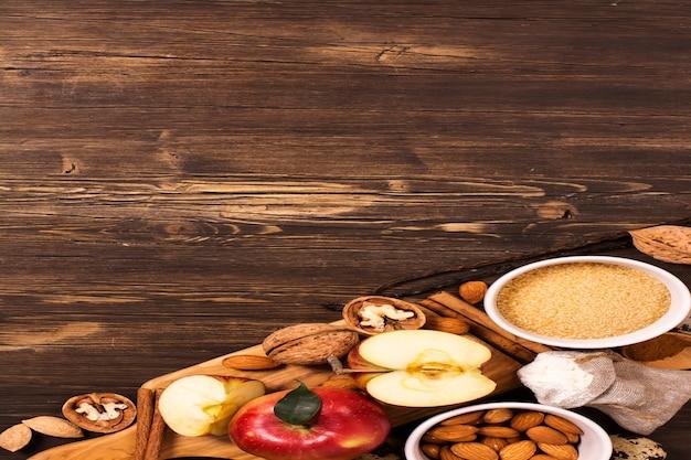 Apfelkuchen ingredients über braunem hölzernem Premium Fotos