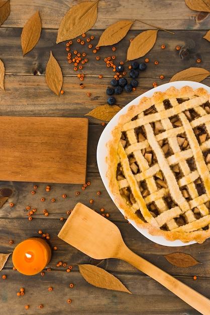 Apfelkuchen nahe schneidebrett zwischen laub und beeren Kostenlose Fotos