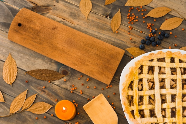 Apfelkuchen nahe schneidebrett zwischen laub Kostenlose Fotos