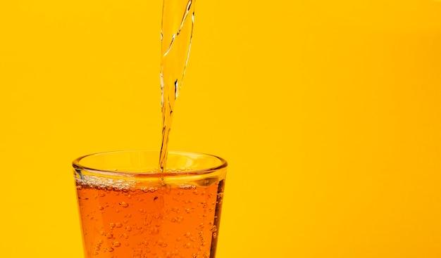Apfelsaft, der in das glas, getrennt auf gelb gießt Premium Fotos
