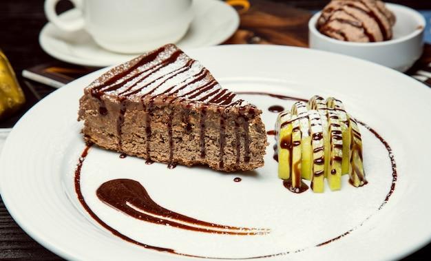 Apfelschokoladen-kakaotorten-kuchenscheibe mit apfelscheiben und schokoladensoße. Kostenlose Fotos