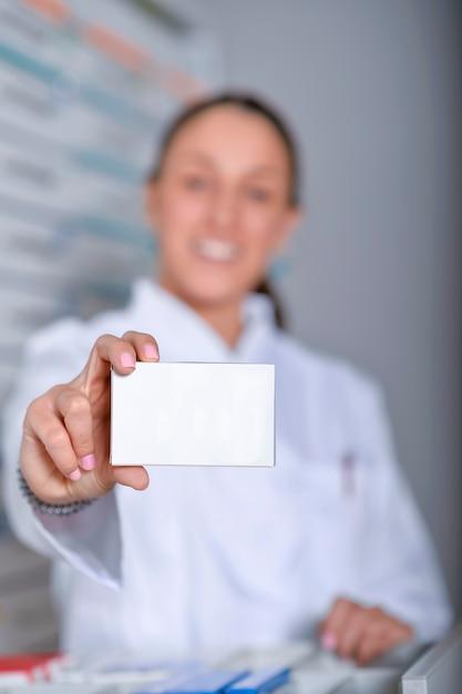 Apotheker, der weißen leeren medizinkasten mit apothekenladenregalen zeigt Premium Fotos