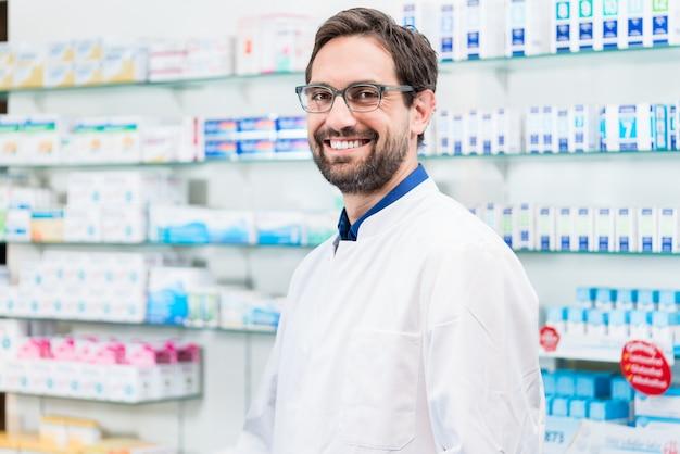 Apotheker in der apotheke, die am regal mit drogen steht Premium Fotos