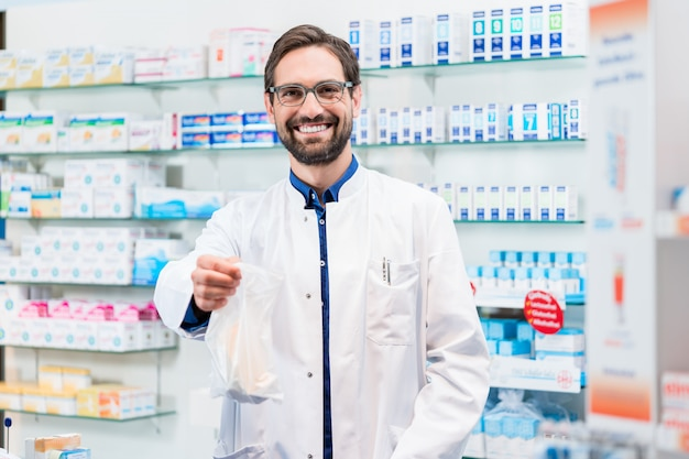 Apotheker in der apotheke, die pharmazeutika in der tasche verkauft Premium Fotos