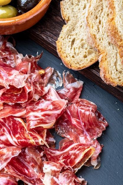 Appetitanregende scheiben iberischer schinken im vordergrund. olivenöl, brot, frische tomaten, oliven. Premium Fotos