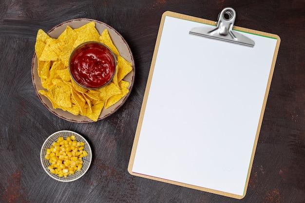 Appetitanregende soße mit nachos klemmbrett und mais Kostenlose Fotos