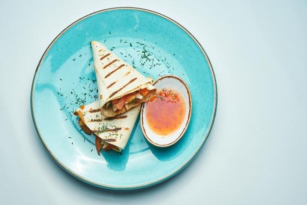 Appetitliche dönerrolle mit fleisch, salat und hausgemachter sauce in dünnem fladenbrot in blauem teller isoliert in grauer oberfläche. östliche küche. geschnittener kebab mit gegrilltem fleisch. Premium Fotos
