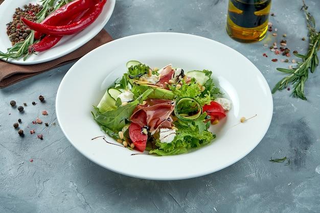 Appetitlicher salat mit jamon, feta-käse, avocado in einem weißen teller Premium Fotos