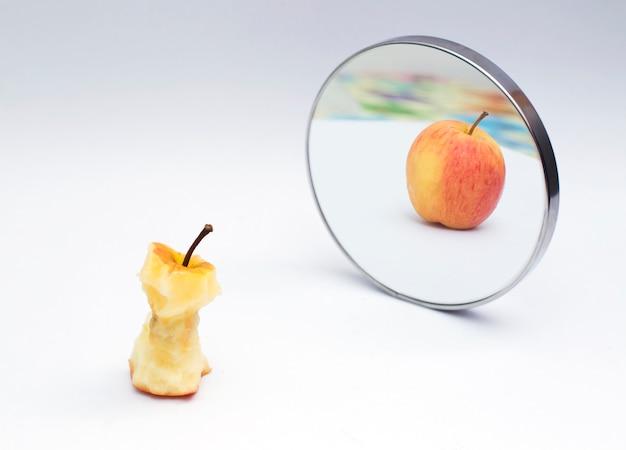 Apple, der im spiegel auf weißem isolathintergrund sich reflektiert Premium Fotos
