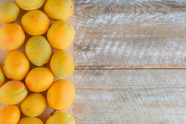 Aprikosen auf holz und schneidebrett, flach gelegt. Kostenlose Fotos