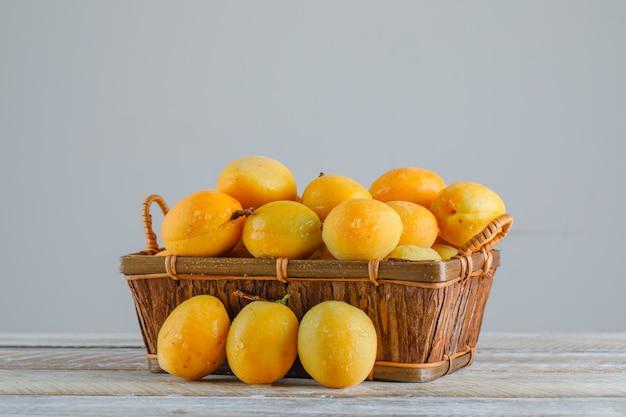 Aprikosen in einem korb auf holztisch. seitenansicht. Kostenlose Fotos