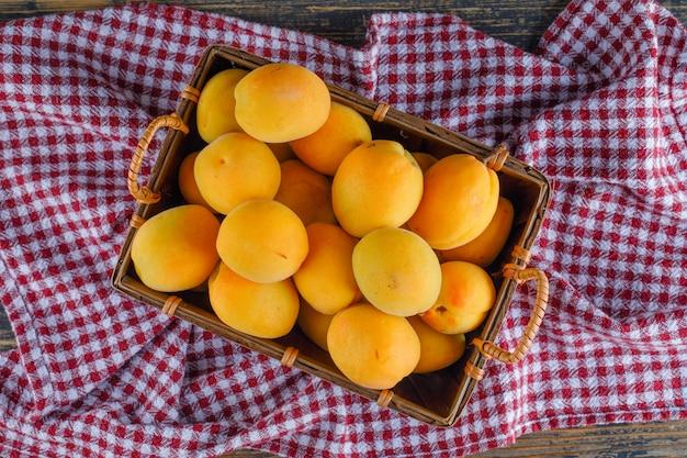 Aprikosen in einem korb auf picknicktuch und holztisch. flach liegen. Kostenlose Fotos