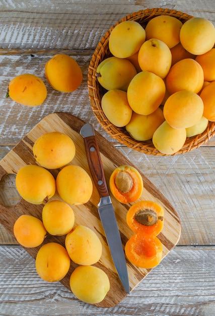 Aprikosen in einem korb mit messer draufsicht auf holz und schneidebrett Kostenlose Fotos
