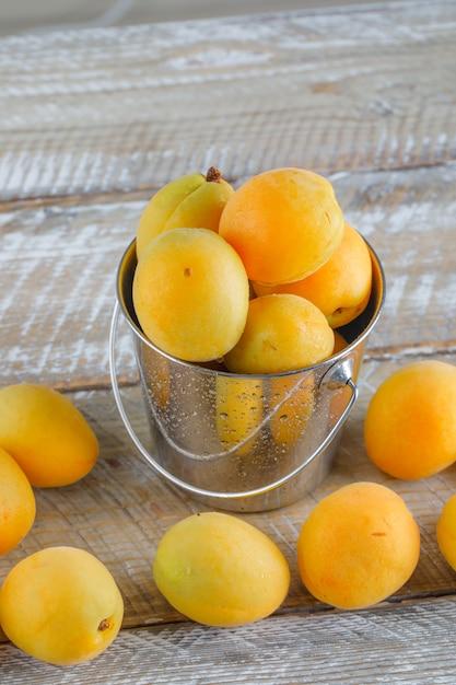 Aprikosen in einem mini-eimer auf holztisch, draufsicht. Kostenlose Fotos