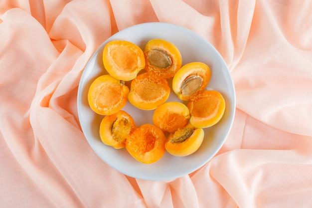 Aprikosen in einem teller. flach liegen. Kostenlose Fotos