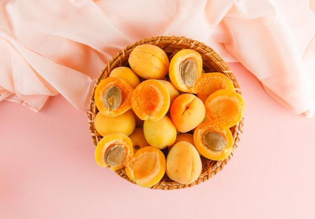 Aprikosen in einem weidenkorb. flach liegen. Kostenlose Fotos