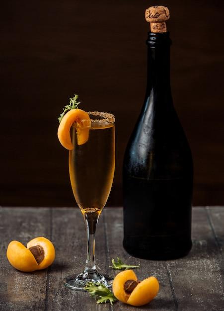 Aprikosenchampagner im champagnerglas, garniert mit aprikosen auf holztheke Kostenlose Fotos