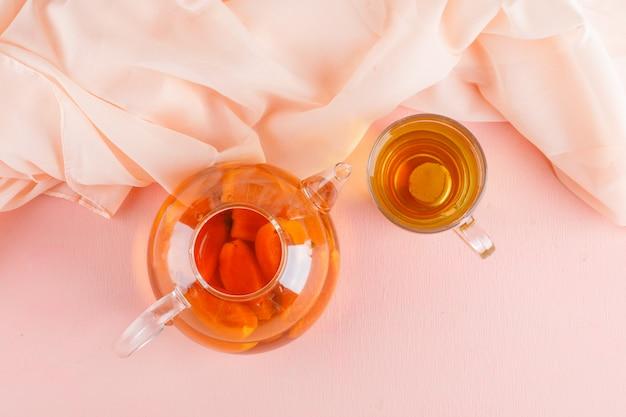 Aprikosentee in teekanne und glasbecher auf rosa und textiltisch, draufsicht. Kostenlose Fotos