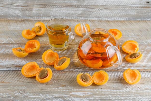 Aprikosentee in teekanne und glasbecher mit aprikosen-draufsicht auf einem holztisch Kostenlose Fotos