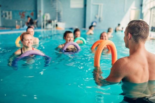 Aqua-aerobic-übungen, frauenklasse mit männertrainer, hallenbad, freizeit Premium Fotos