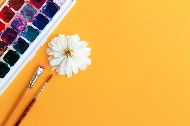 Aquarellfarbe, -pinsel und -blume mit den weißen blumenblättern auf einem gelben hintergrundkonzept der kreativität Premium Fotos