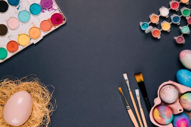 Aquarellfarbenkasten und plastikflasche; osterei; pinsel auf schwarzem hintergrund Kostenlose Fotos