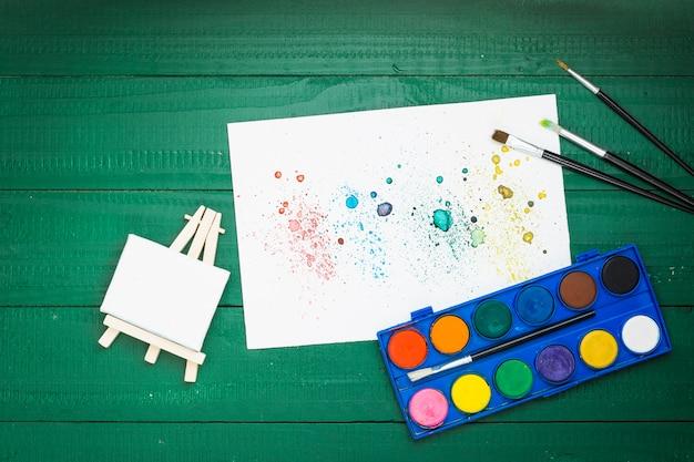 Aquarellmalereiausrüstung und beflecktes strukturiertes papier auf grünem hintergrund Kostenlose Fotos