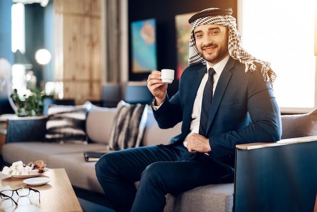 Arab trinkt kaffee auf der couch im hotelzimmer. Premium Fotos
