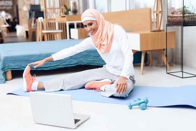 Arabische frau, die gymnastik im schlafzimmer tut. Premium Fotos