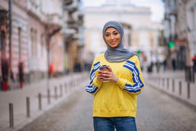 Arabische frau im hijab ouside in trinkendem kaffee der straße Kostenlose Fotos