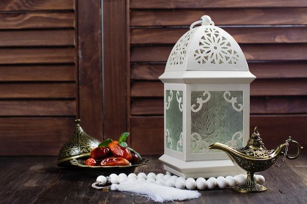 Arabische laterne, datteln, aladinlampe und rosenkranz auf holz Premium Fotos