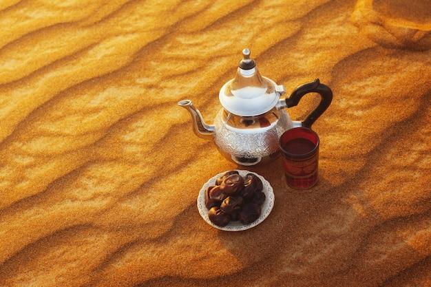 Arabische teekanne, tasse und datteln stehen auf dem sand in der wüste Premium Fotos