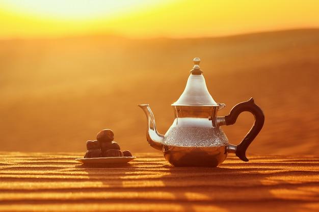 Arabische teekanne und daten in der wüste bei einem schönen sonnenuntergang, der ramadan symbolisiert Premium Fotos