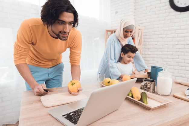 Arabischer auftritt in der modernen kleidung in der küche mit einem laptop. Premium Fotos