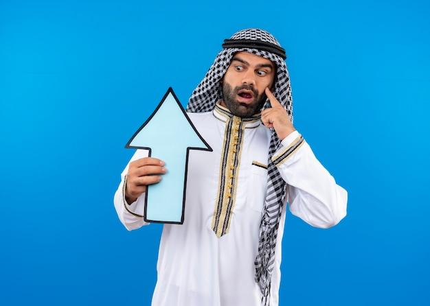 Arabischer mann in traditioneller kleidung, der großen blauen pfeil hält, der ihn überrascht und erstaunt betrachtet, der über blauer wand steht Kostenlose Fotos