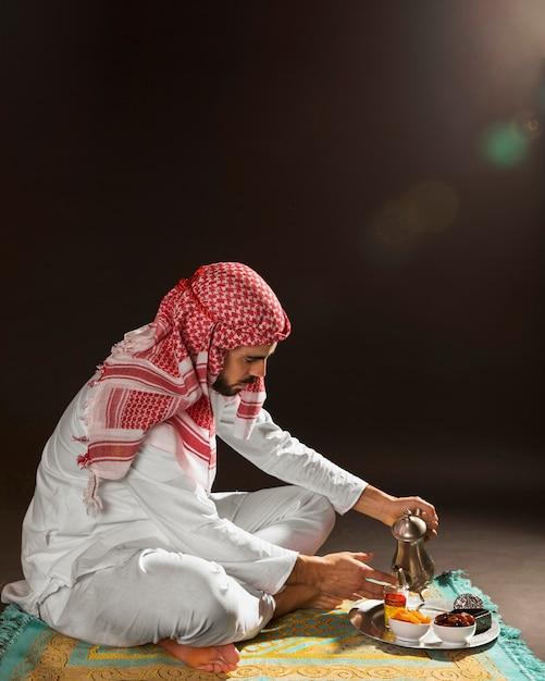 Arabischer mann mit auslaufendem tee der kandora Kostenlose Fotos