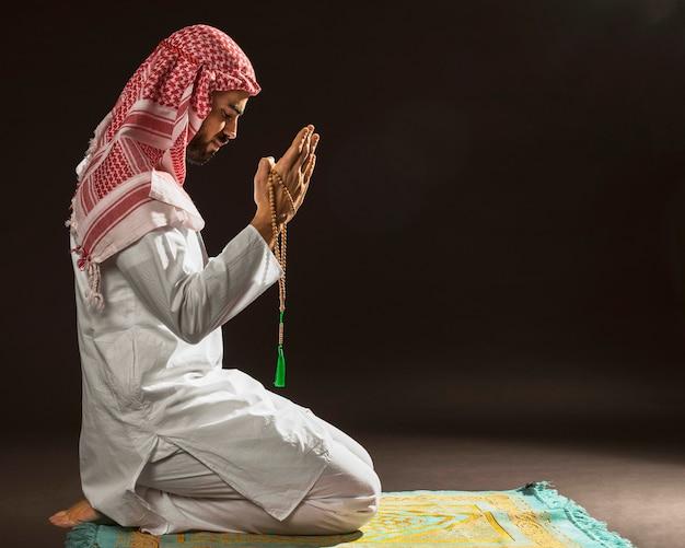 Arabischer mann mit der kandora, die auf gebetsteppich sitzt Kostenlose Fotos