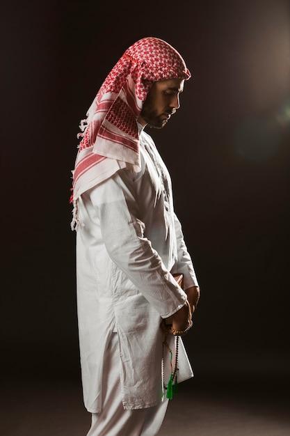 Arabischer mann mit kandora stehend und betend