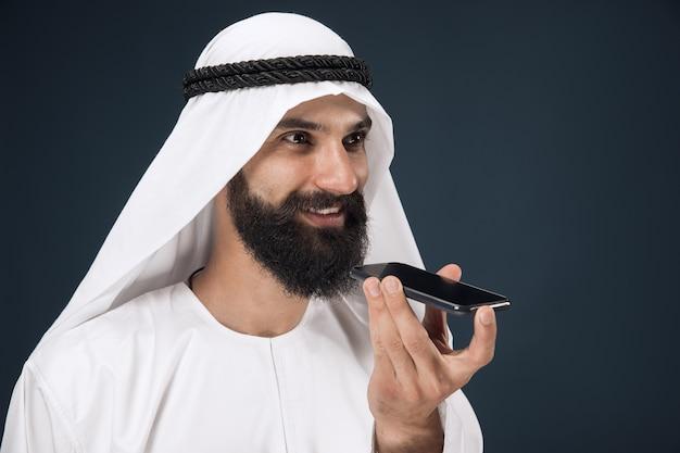 Arabischer saudischer mann auf dunkelblauem studiohintergrund Kostenlose Fotos