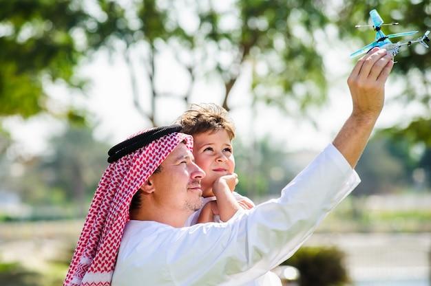 Arabischer sohn und vater drinnen posieren. Premium Fotos