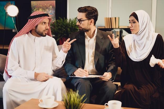 Arabisches paar an der rezeption des therapeuten argumentiert. Premium Fotos