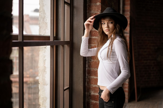 Arbeiten sie das portrait des jungen schönen überzeugten tragenden hutes der frau um und herein aufwerfen am fenster Premium Fotos
