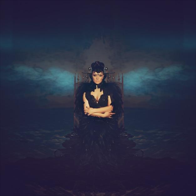 Arbeiten sie gotisches porträt eines schönen brunette in einem langen schwarzen kleid um, das von den rabenfedern gemacht wird. halloween Premium Fotos