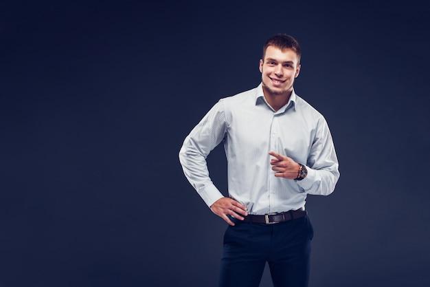 Arbeiten sie jungen ernsten mann in abgestreiftem hemd zeigt finger um und lächeln und schauen. Premium Fotos