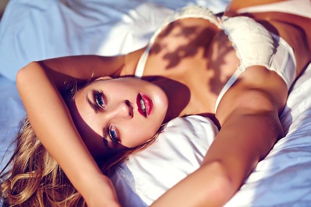 Arbeiten sie porträt des schönen sexy jungen erwachsenen blonden frauenmodells um, das die weiße erotische wäsche trägt, die morgens auf sonnenaufgang des betts liegt Kostenlose Fotos