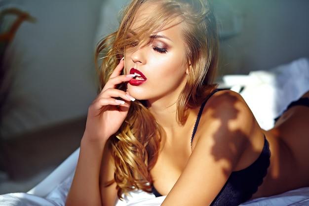 Arbeiten sie porträt des schönen sexy jungen erwachsenen blonden frauenmodells um, welches die schwarze erotische wäsche trägt, die auf bett bei sonnenuntergang liegt Kostenlose Fotos