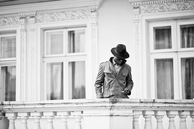 Arbeiten sie porträt des schwarzafrikanermannes auf grünem mantel und schwarzem hut, aufenthalt auf dem balkon der gelben villa um. schwarzweiß-foto Premium Fotos