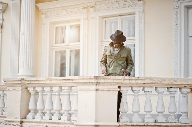Arbeiten sie porträt des schwarzafrikanermannes auf grünem mantel und schwarzem hut, aufenthalt auf dem balkon der gelben villa um Premium Fotos