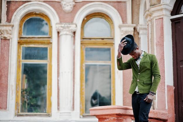 Arbeiten sie porträt des schwarzafrikanermannes auf grünem samtjackenaufenthalt auf treppe um und tragen sie seine alte villa des schwarzhuthintergrundes. Premium Fotos